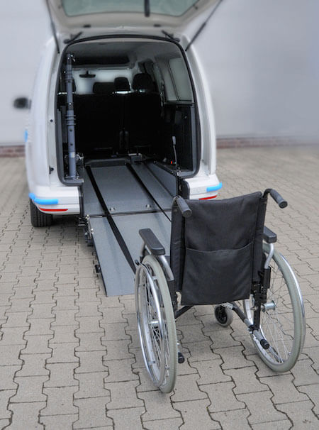 A winch and restraint that pulls a wheelchair into the back of a van.